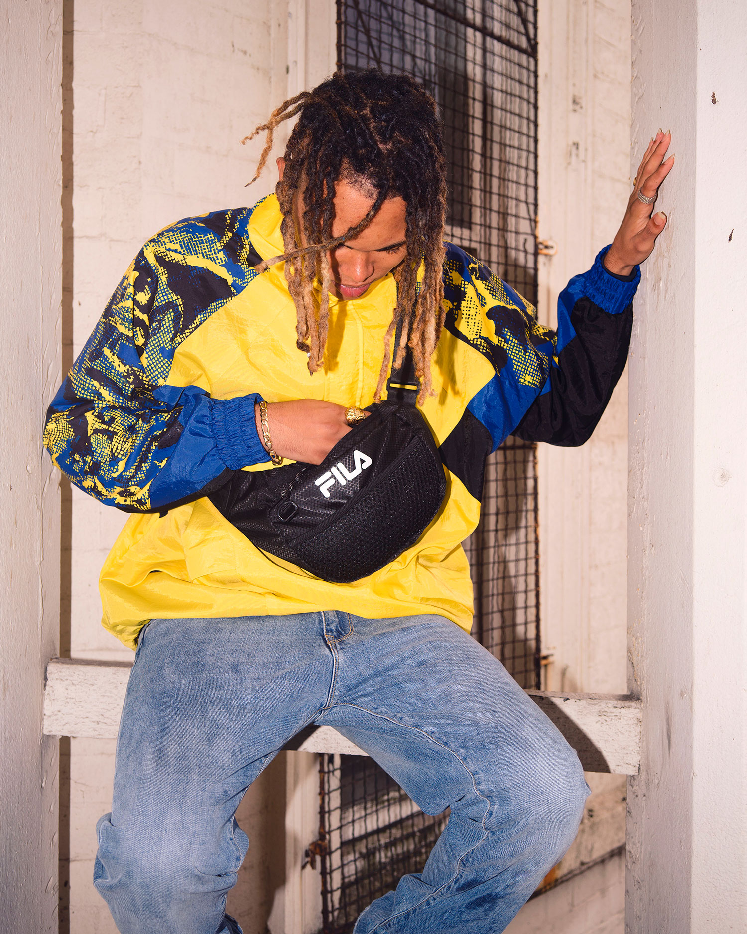 A man wearing a blue and yellow FILA Apparel Pullover Jacket